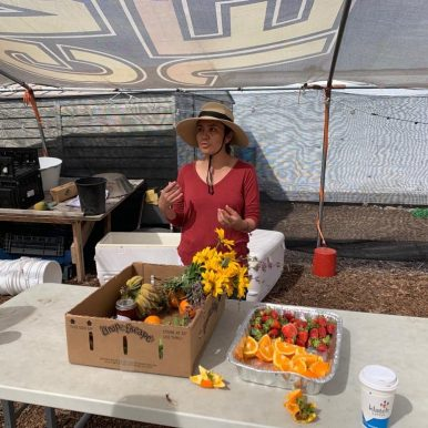 Lucy, of Huerta del Valle, explaining how the garden supports the community, including giving free produce to those in need.